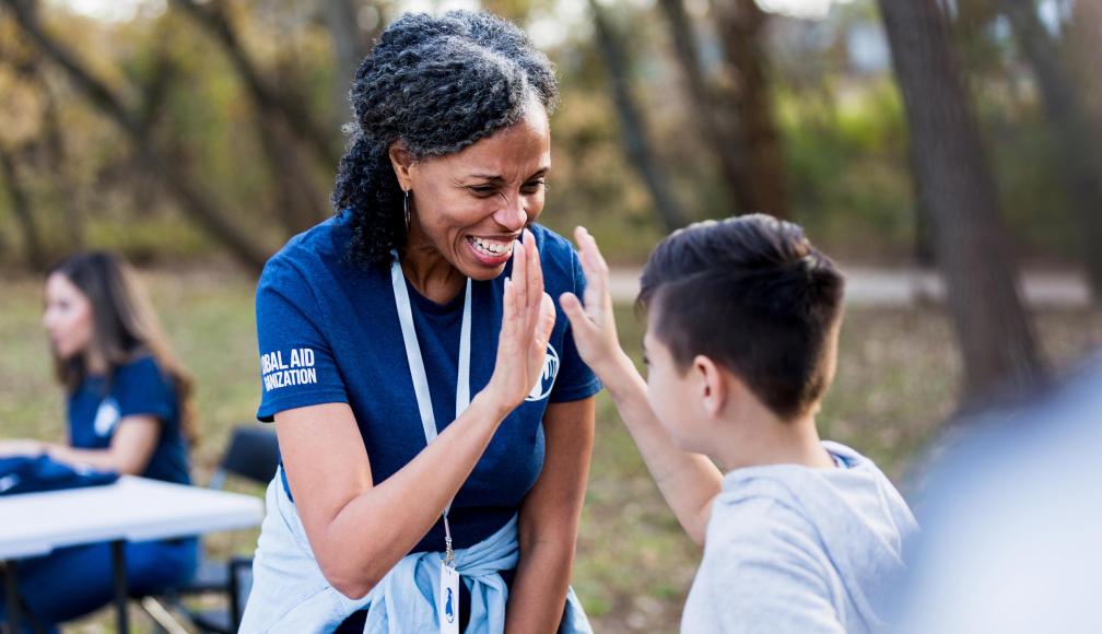 non-profit-black-organization-mature-woman-high-five-child-at-park